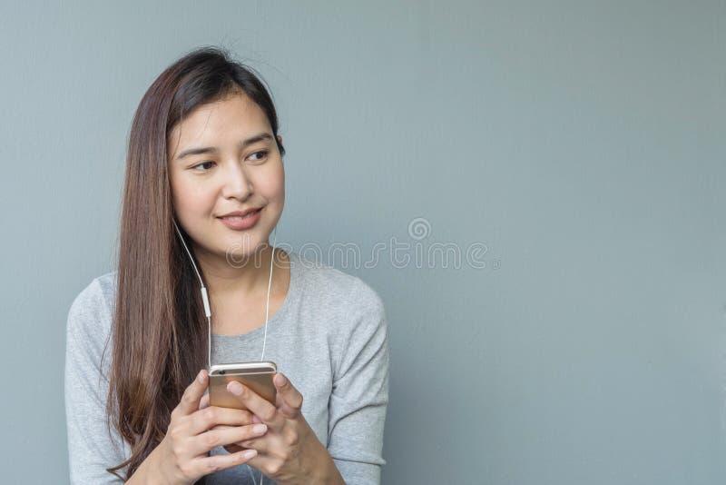 La femme asiatique de plan rapproché s'asseyant pour écoutent musique de comprimé avec l'écouteur dans l'émotion heureuse sur le  images libres de droits