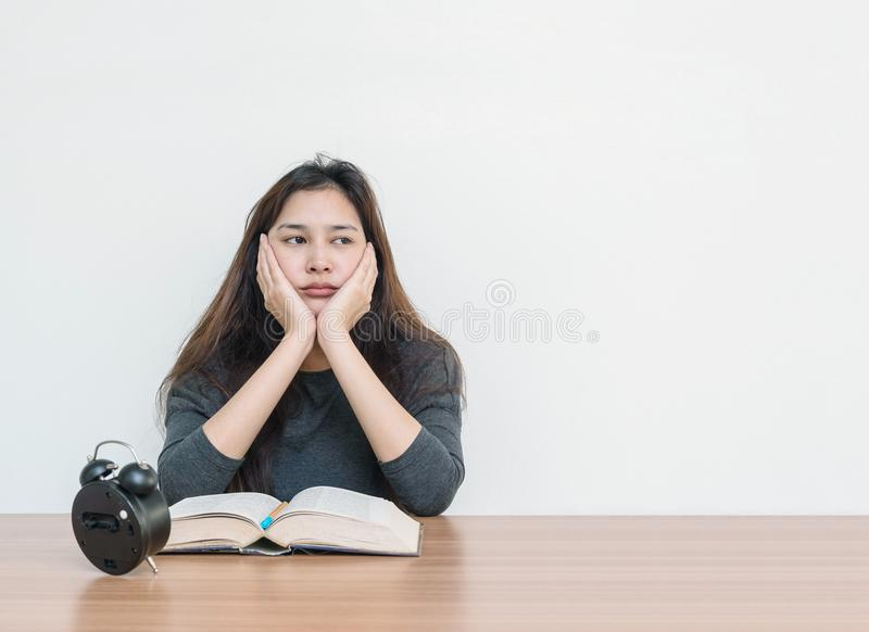 La femme asiatique de plan rapproché s'asseyant pour a lu un livre avec émotion ennuyeuse et le visage de pensée sur le mur de ta photos libres de droits