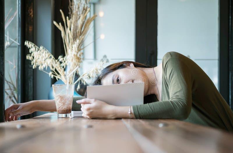La femme asiatique de plan rapproché s'est trouvée sur le contre- bureau en bois pour lire un livre dans le café avec le visage h photo libre de droits