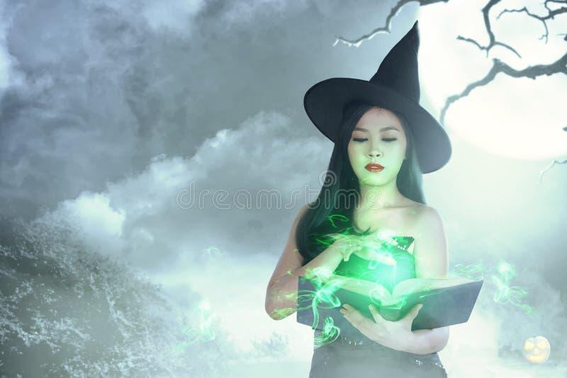 La femme asiatique de sorcière dans le chapeau apprend le charme du livre magique image libre de droits