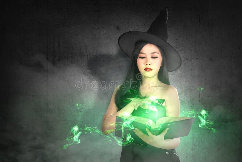 La femme asiatique de sorcière dans le chapeau apprend le charme du livre magique photographie stock
