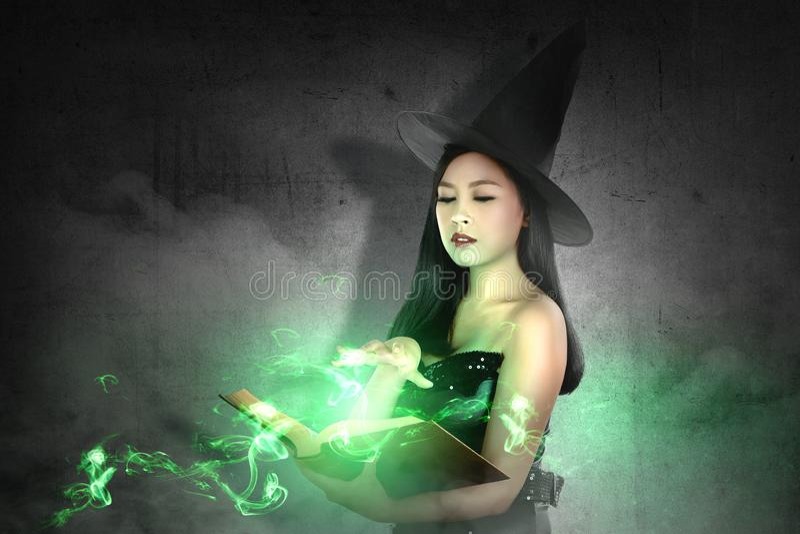 La femme asiatique de sorcière dans le chapeau apprend le charme du livre magique photos stock