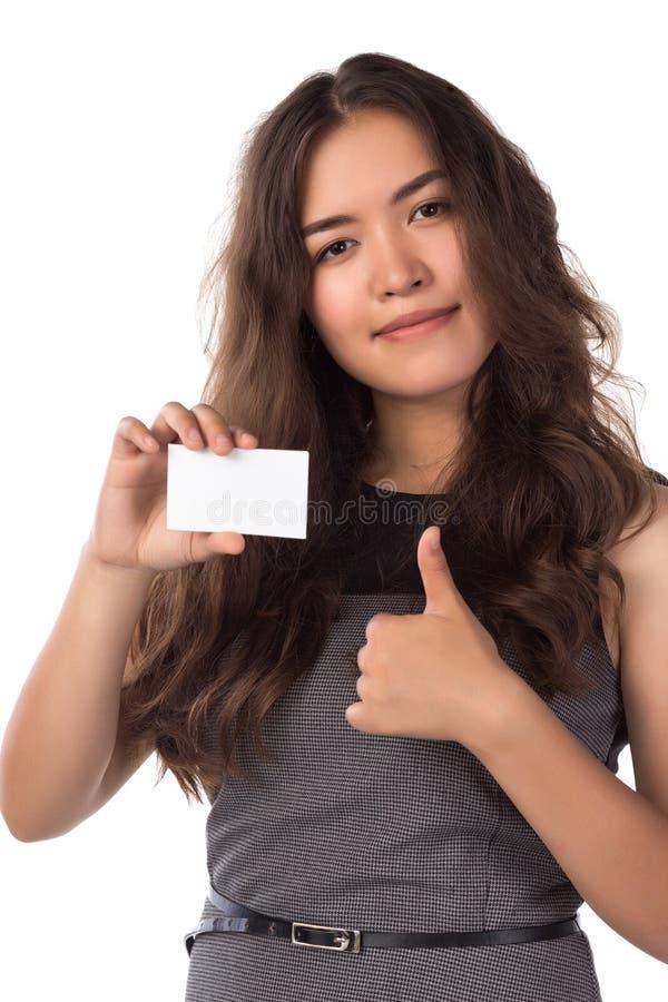 La femme asiatique de sourire de jeunes tenant une carte vierge, expositions manie maladroitement vers le haut du geste photos libres de droits