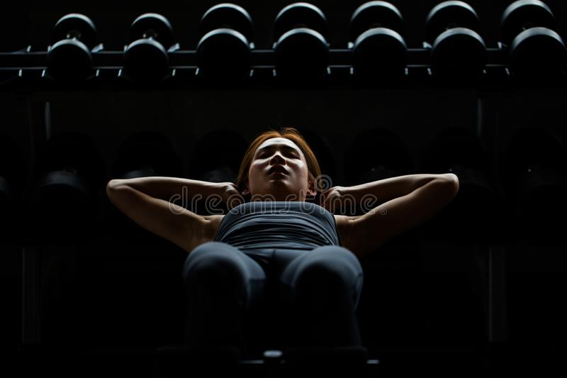 la femme asiatique de sport que faire se reposent se lève sur l'étagère d'haltères dans le St de forme physique photographie stock libre de droits