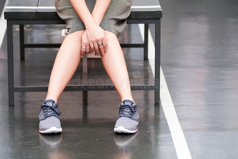 La femme asiatique est utilisante et examinante l'espadrille dans le magasin de chaussures avant pour l'acheter photographie stock