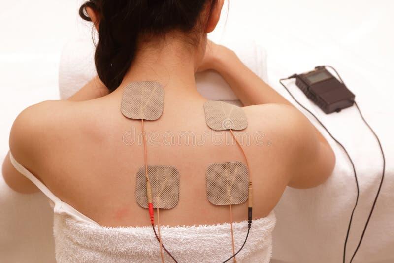 La femme asiatique fait le massage d'élém. élect. - stimulation images stock