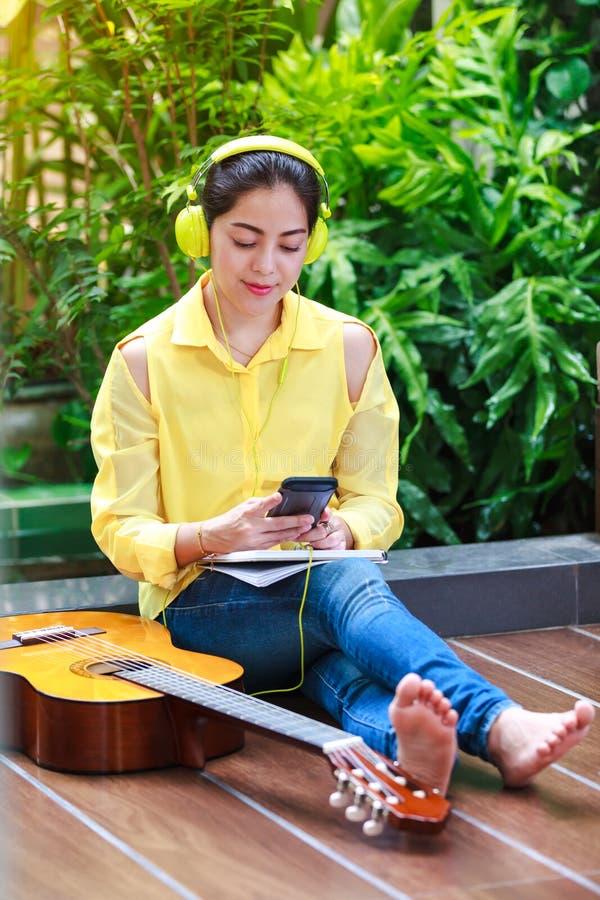 La femme asiatique ont plaisir à passer en revue l'Internet au téléphone intelligent images libres de droits