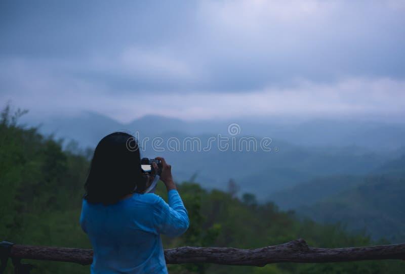 La femme asiatique prennent une photo au point de vue naturel de montagne avec le brouillard photographie stock