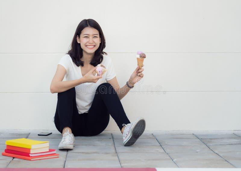 La femme asiatique s'asseyent et détendent avec la crème glacée  photo stock