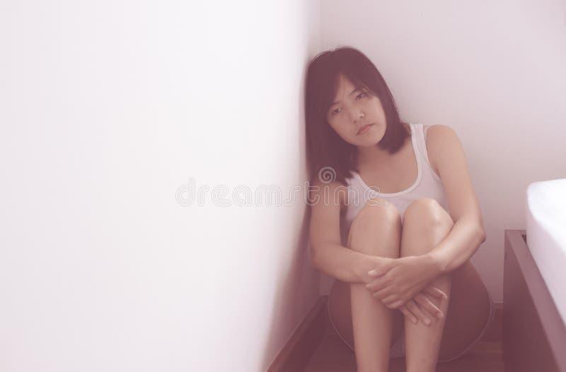 La femme asiatique s'assied et les étreintes ses genoux jusqu'à la dépression de coffre ont un mal de tête dans sa chambre à couc images stock