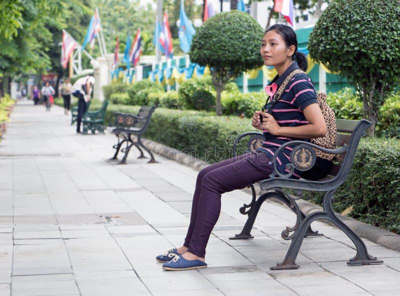 La femme asiatique s'assied sur un banc photo libre de droits