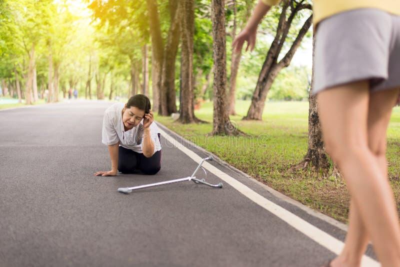 La femme asiatique supérieure avec la séance faible sur le plancher après être tombé vers le bas, femelle salut et l'appui image libre de droits