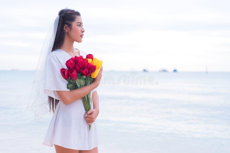 La femme asiatique tenant des fleurs et attendant quelqu'un font son hasard photos stock