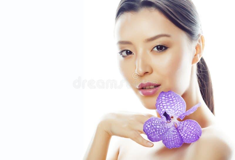 La femme assez asiatique de jeunes avec la fin pourpre d'orchidée de fleur a isolé la station thermale, concept du jour de la fem photos libres de droits