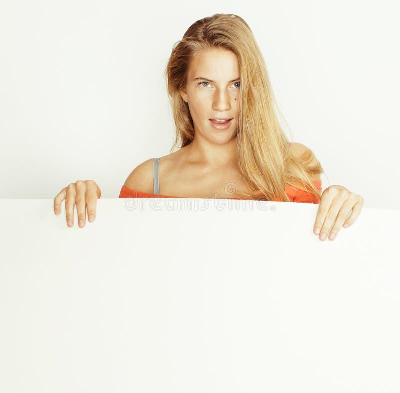 La femme assez blonde de jeunes tenant le conseil blanc vide avec le copyspace a isolé le sourire haut étroit images libres de droits
