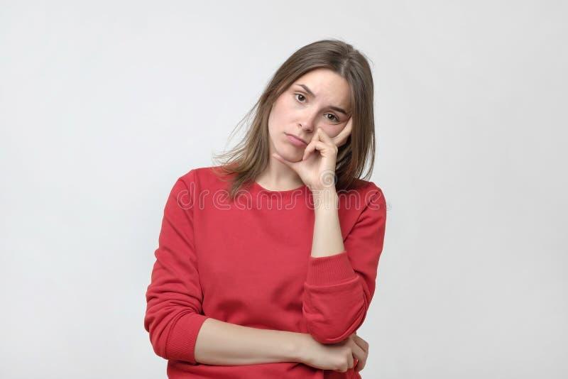 La femme assez caucasienne dans le chandail rouge est fatiguée ou ennuyeuse Elle ne veulent pas travailler ou étudier image libre de droits