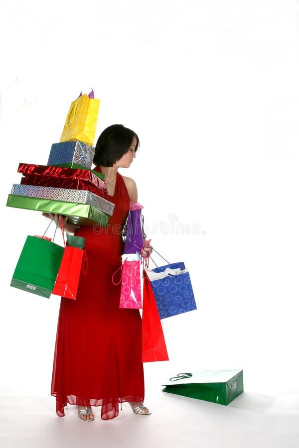 La femme assez jeune a chargé vers le bas avec des sacs de cadeau photo stock