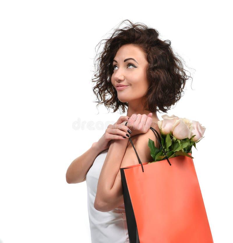 La femme assez jeune de brune avec le panier et les roses roses fleurit images stock