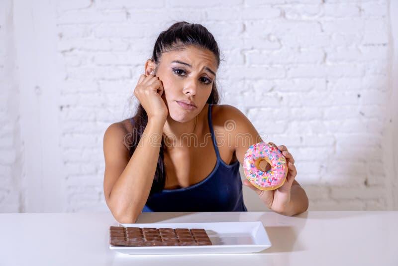 La femme assez latine regardant le chocolat et des butées toriques a fatigué des restrictions de régime image libre de droits