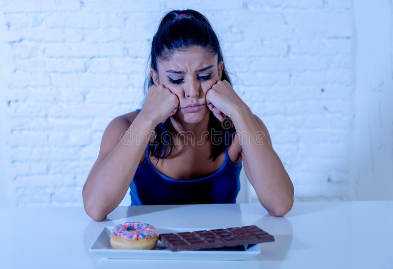 La femme assez latine regardant le chocolat et des butées toriques a fatigué des restrictions de régime photos libres de droits