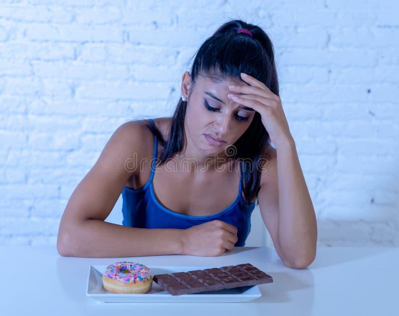 La femme assez latine regardant le chocolat et des butées toriques a fatigué des restrictions de régime image stock