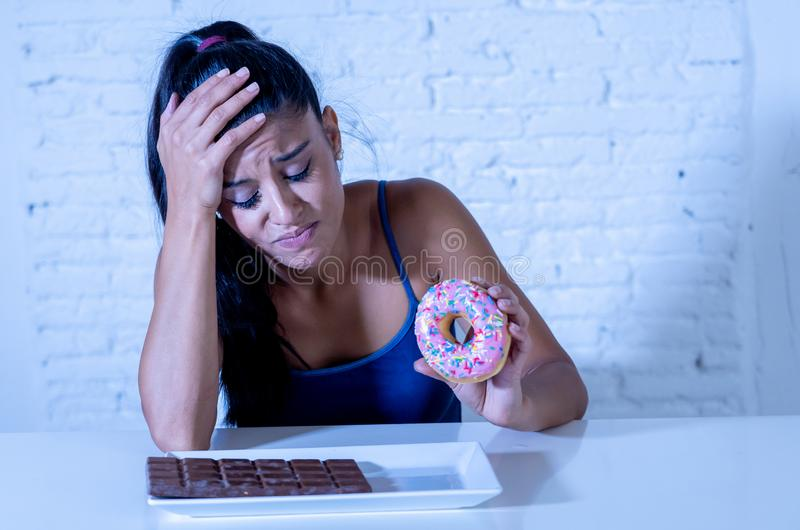 La femme assez latine regardant le chocolat et des butées toriques a fatigué des restrictions de régime images stock