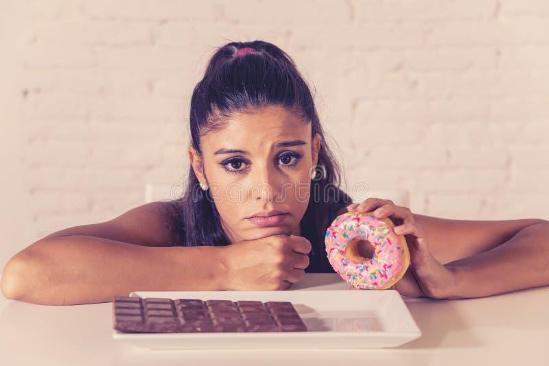 La femme assez latine regardant le chocolat et des butées toriques a fatigué des restrictions de régime images libres de droits