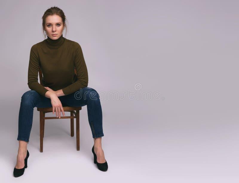 La femme assez occasionnelle s'assied sur une chaise photo stock