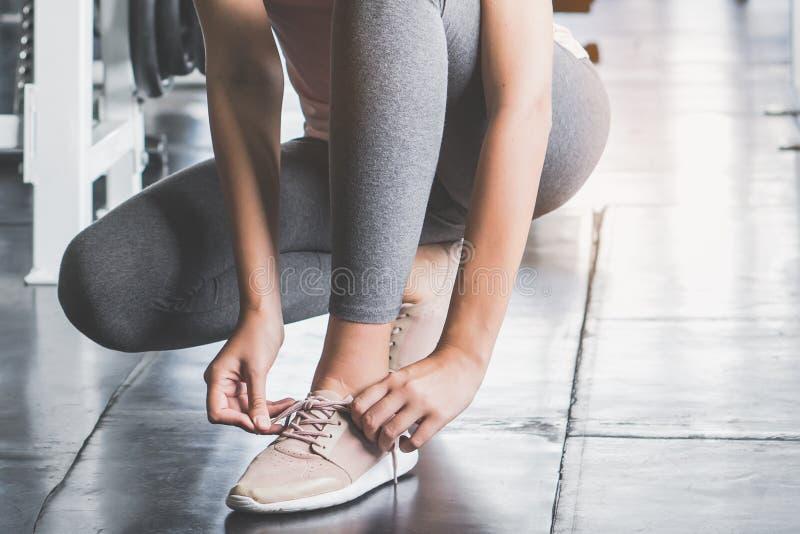 La femme attachant la dentelle disposent à s'exercer dans la forme physique photo stock