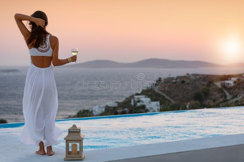 La femme attirante à la piscine apprécie le coucher du soleil au-dessus de la mer Méditerranée photo libre de droits