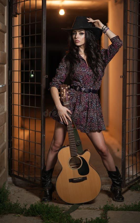 La femme attirante avec le regard de pays, a à l'intérieur tiré, style campagnard américain Fille avec le chapeau et la guitare d images libres de droits