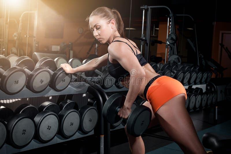 La femme attirante d'ajustement établit avec des haltères comme forme physique conceptuelle au-dessus du fond foncé photo stock