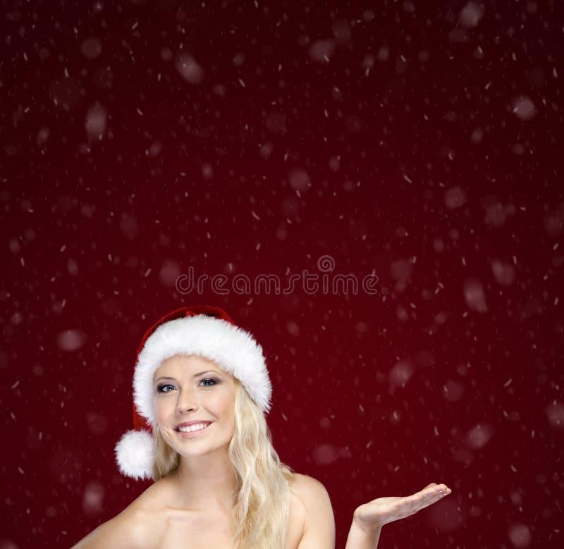 La femme attirante dans le capuchon de Noël fait des gestes la paume vers le haut photo stock
