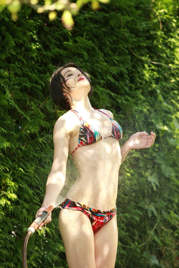 La femme attirante dans le jardin prend une douche froide photographie stock libre de droits