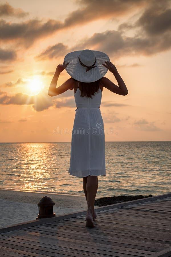 La femme attirante dans la robe et le chapeau blancs apprécie le coucher du soleil image stock