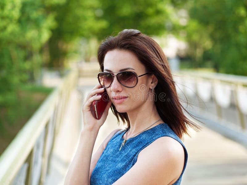 La femme attirante de brune dans les lunettes de soleil et la robe de blues-jean fait se surpasser la conversation téléphonique é images libres de droits