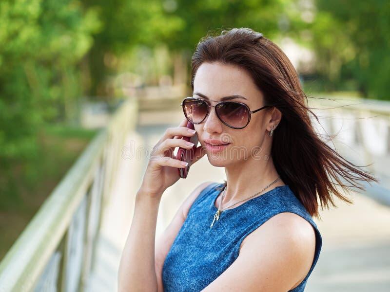 La femme attirante de brune dans les lunettes de soleil et la robe de blues-jean fait se surpasser la conversation téléphonique é images stock