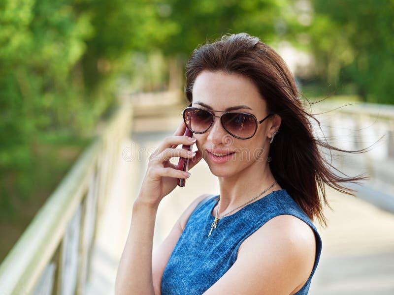 La femme attirante de brune dans les lunettes de soleil et la robe de blues-jean fait se surpasser la conversation téléphonique é image stock