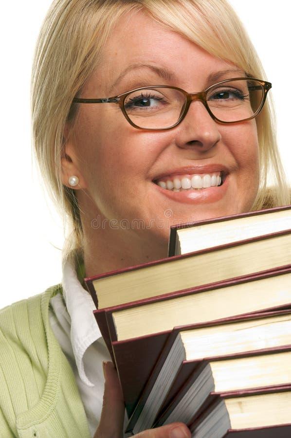 La femme attirante de sourire porte la pile de livres photographie stock