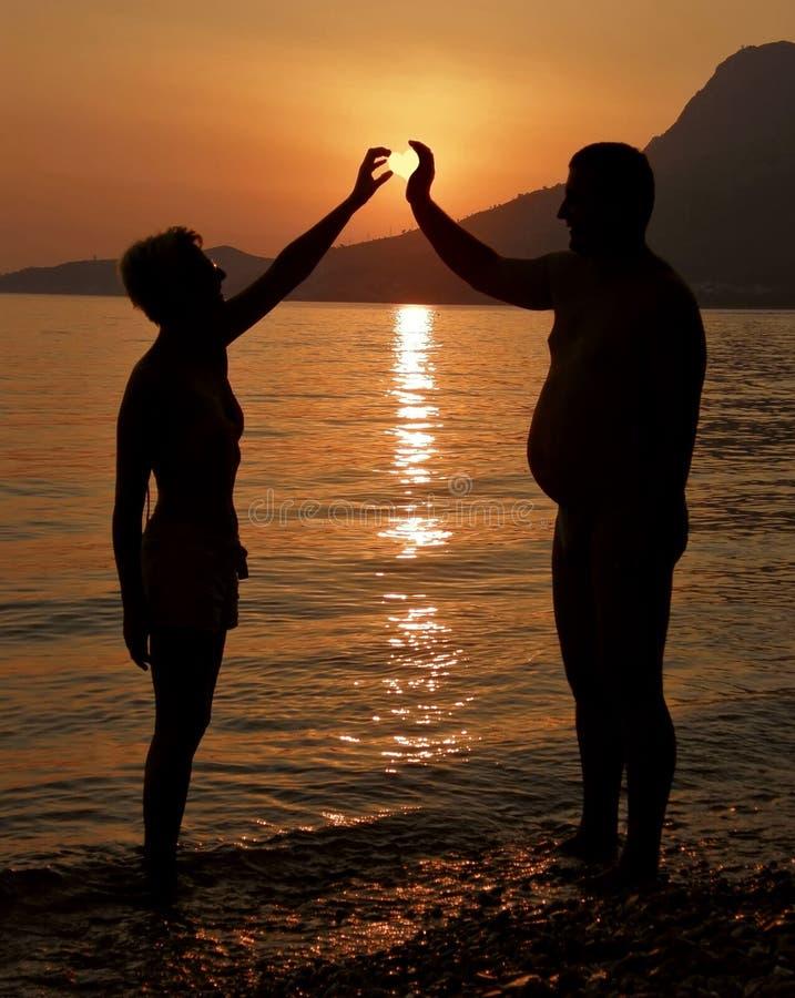 La femme attirante et le gros homme avec le soleil aiment un coeur photo stock