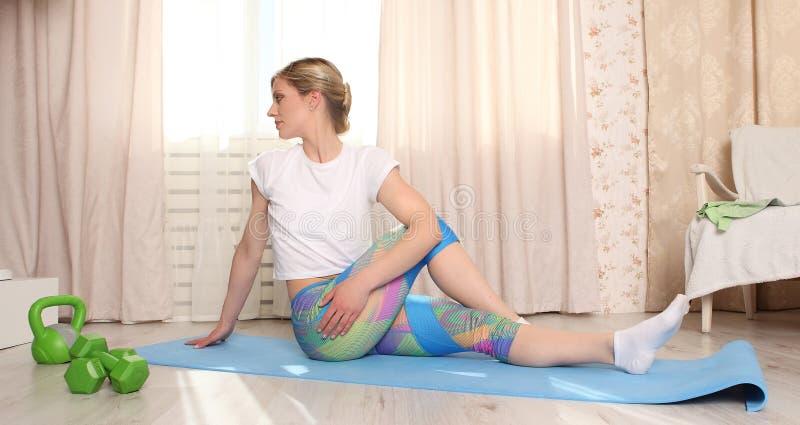La femme attirante font la forme physique étirant à la maison l'intérieur dans le salon photographie stock