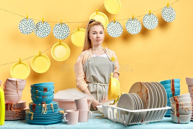 La femme attirante heureuse avec le regard amical nettoie la cuisine photo libre de droits