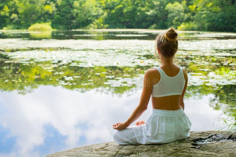 La femme attirante pratique le yoga se reposant dans la pose de lotus sur la pierre près du lac photographie stock libre de droits
