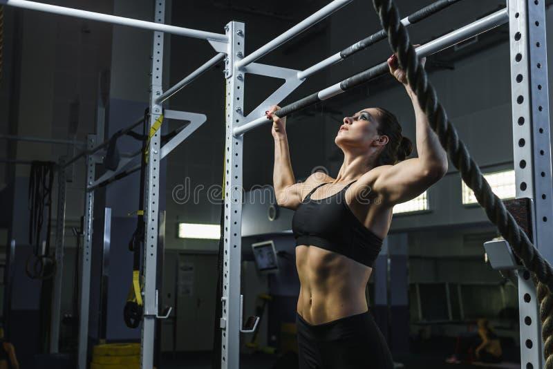 La femme attirante puissante CrossFit que l'entraîneur tirent se lève pendant la séance d'entraînement photo stock