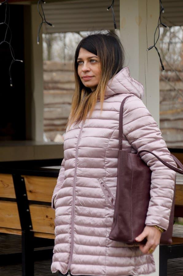 La femme attirante se tient dans un nea piqué de veste de rose d'hiver image stock