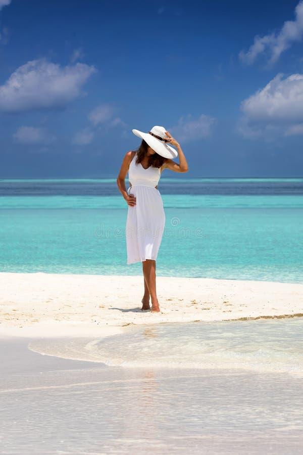 La femme attirante se tient sur un banc de sable avec les eaux de turquoise et le ciel bleu image stock