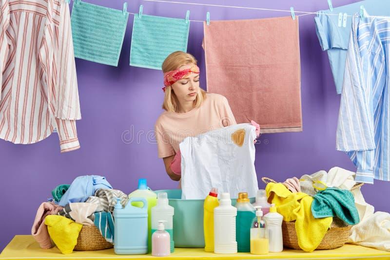 La femme au foyer blonde contrariée a trouvé la tache, tache sur le T-shirt blanc photos stock