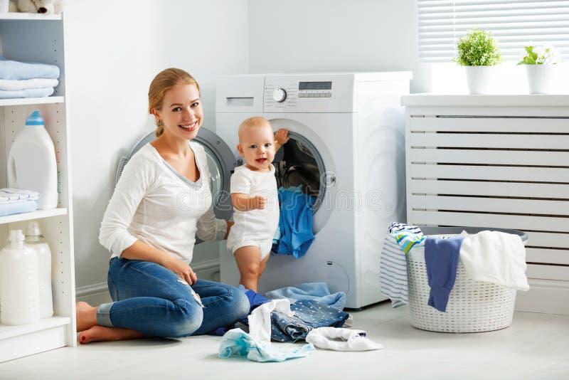 La femme au foyer de mère avec le bébé s'est engagée dans des vêtements de pli de blanchisserie dans image stock