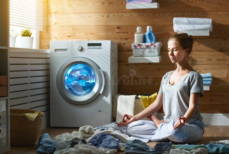 La femme au foyer fatiguée de femme dans l'effort médite dans la pose de yoga de lotus dedans images stock