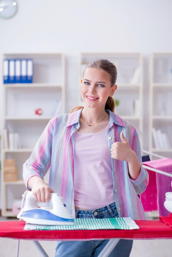 La femme au foyer heureuse faisant repasser à la maison image stock